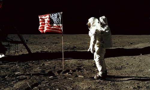 EARTH, THE MOON, Sea of Tranquility -- 20 Jul 1969 -- Astronaut Edwin E Aldrin, Jr, lunar module pilot of the first lunar landing mission, poses for a photograph beside the deployed United States flag during an Apollo 11 Extravehicular Activity (EVA) on the lunar surface. The Lunar Module (LM) is on the left, and the footprints of the astronauts are clearly visible in the soil of the Moon. While astronauts Armstrong and Aldrin descended in the LM, the 'Eagle', to explore the Sea of Tranquility region of the Moon, astronaut Michael Collins, command module pilot, remained with the Command and Service Modules (CSM) Columbia in lunar-orbit -- Picture by Lightroom Photos / NASA / Neil Armstrong